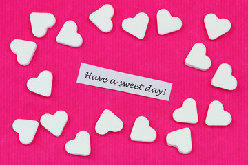 Have a sweet day with sugar hearts on pink surface