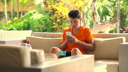 Young teenager sitting with smartphone and soda on sofa at home