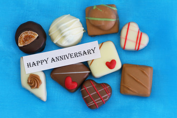 Happy Anniversary card with chocolates on blue background
