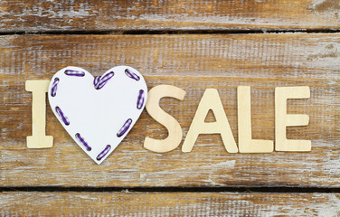 I love sale sign on rustic wooden surface