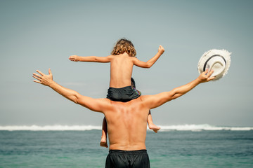 father and son playing on the beach at the day time