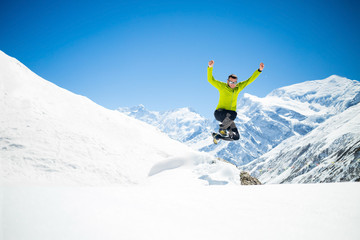 Happy man jumping in winter mountains