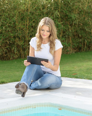Woman by the pool with tablet