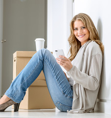 Happy woman texting in new home