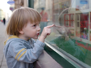 Boy pointing a favorite toy through the showcase
