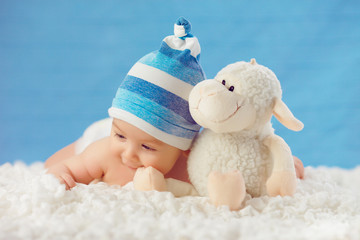 Cmile baby in hat, hugging toy on a white bedspread, on a blue b