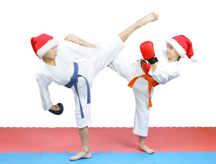 Athletes in Santa hats with different belts beat each other