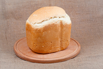 Bread on a wooden board on a background of the canvas.
