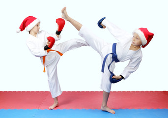 Children in kimono and Santa hats standing on the mat