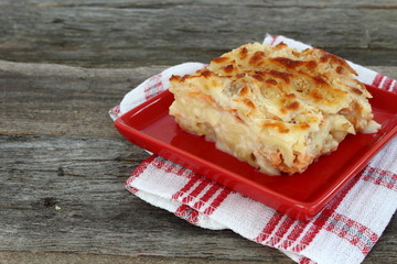 Macaroni gratin with salmon in a red plate