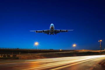 flying passenger jet plane above traffic light on express ways u