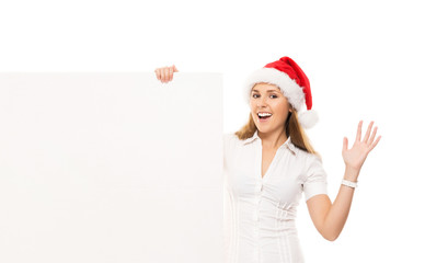Happy teenage girl in a Christmas hat with a blank billboard