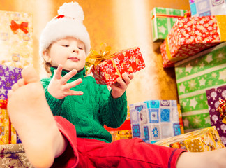 boy in holiday hat holding gift box at colorful background