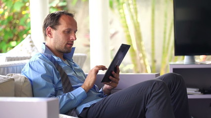 Young  businessman working with detachable tablet on sofa