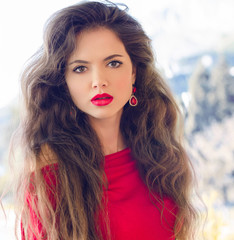 Beautiful young girl with red lips, long wavy hair wearing in re