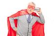 Shocked senior superhero with a tin can phone
