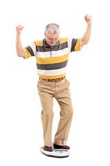 Joyful senior measuring his weight