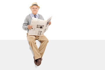 Senior holding a newspaper seated on a panel