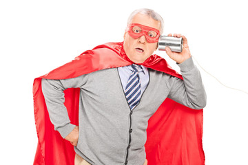 Shocked senior superhero with a tin can phone