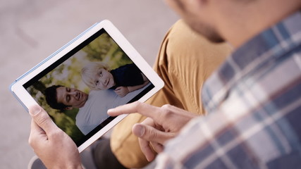 Man looks at photos of him and son having a good time on tablet