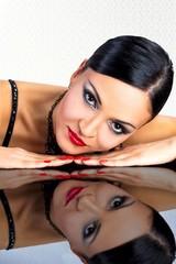 Beautiful black hair woman,lying on reflective table.