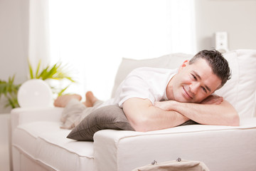 man smiling to camera relaxing in his living room