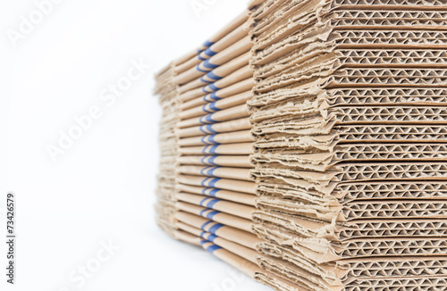Stacked brown corrugated cardboard boxes isolated on white - 73426579