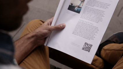 Man scanning qr code from magazine with smartphone
