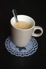 grijs bruine koffiekop met zwart houten achtergrond