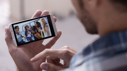 Man uses smartphone to look at photos of his friends together