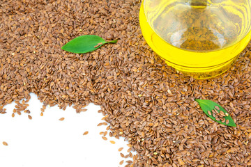 Flax seeds and glass bottle of oil with green leaves