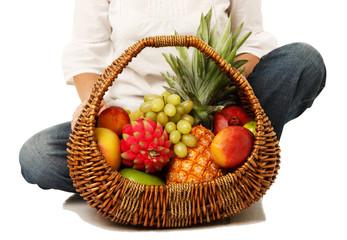 Fruit basket in hands of women.