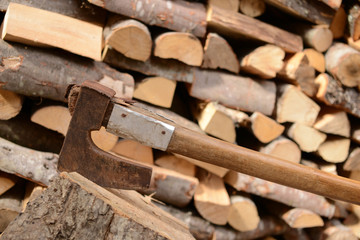 A pile of woods. Firewood with axe .