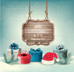 Winter background with gift boxes and a wooden ornate Merry chri