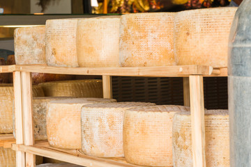 series of round forms of aged cheese for sale in the local marke