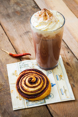 Snail and hot chocolate on napkin and wooden background