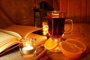 Hot mulled wine in the cup and open book.