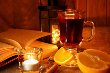 Hot mulled wine in the cup and open book..