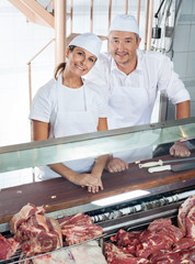 Friendly Butchers Standing At Meat Counter