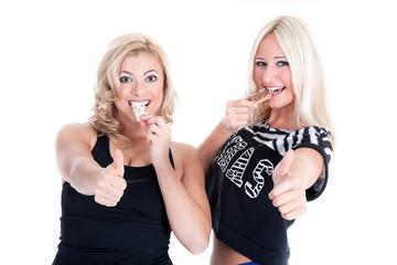 Zwei iFrauen essen Müsliriegel und halten lächelnt Daumen hoch