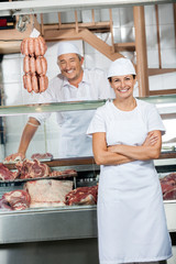Butchers At Display Cabinet In Butchery