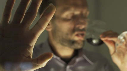 Sad man drinking wine and holding hand on window
