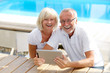 Different aged couple with a tablet pc outside