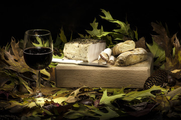 Autumnal still life composition with lard, bread and red wine