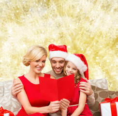 happy family in santa hats with greeting card