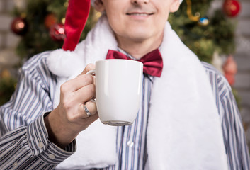 Portrait of young happy man in Santa hat with cup of tea
