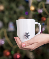 cup of tea in female hands on a background of New Year tree