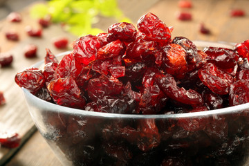 Dried cranberries in a glass bowl on wooden background