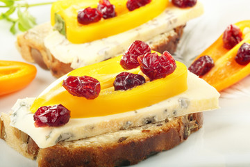 Sandwich with mold cheese, sweet peppers and cranberries on whit