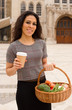 young woman with a coffee and a basket of groceries.